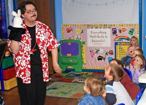 Family and children's comedy magician and ventriloquist, The Astonishing Mr. Pitts, entertains a group of pre-school children at an early learning center in San Antonio, Texas.