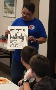 David Pitts, professional cartoonist and graphic artists teaches cartooning to a group of children at a Texas library.