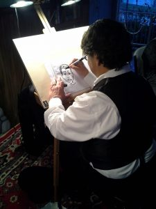 A photograph of David Pitts drawing caricatures.